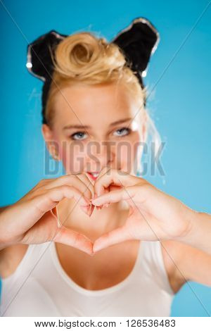 Pin up and retro style. Valentines day. Young smiling woman hairstyle making hands heart sign symbol on blue background.