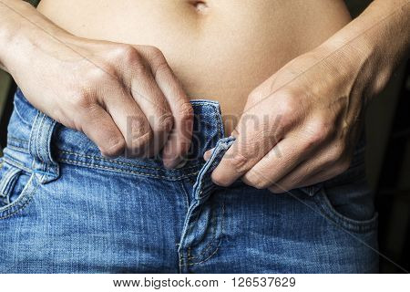 Slender young woman unbuttons the metal clasp button on blue jeans