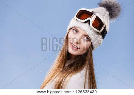 Woman skier girl wearing warm clothing ski googles portrait. Winter sport activity. Beautiful sportswoman on blue studio shot