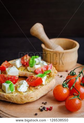 Italian appetizer Friselle. Italian dried bread Friselle on wooden board with tomatoes cherry, basil and peppercorns. Italian food. Healthy vegetarian food. Antipasti concept. Selective focus.