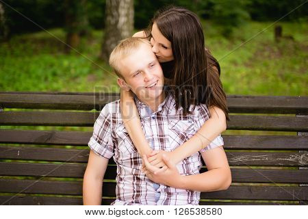 Young teen couple sitting together and lovely hugging on the bench outdoors