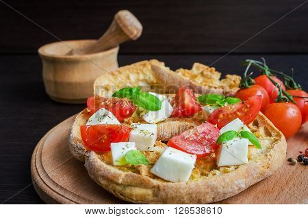 Italian appetizer Friselle. Italian dried bread Friselle on wooden board with tomatoes cherry, basil and pepper. Italian food. Healthy vegetarian food. Antipasti concept. Selective focus.