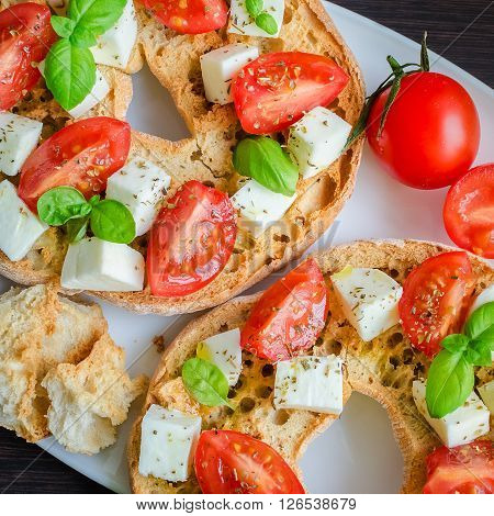 Italian starter friselle. Classical frisella tomato, cheese mozzarella and basil with oregano and olive oil. Dried bread called freselle on white plate. Italian food. Healthy vegetarian food.