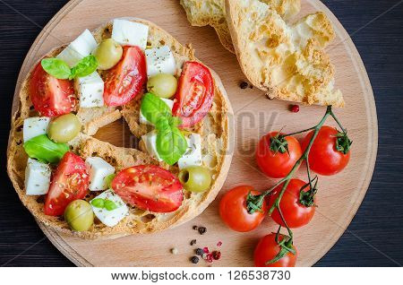Italian appetizer Friselle. Italian dried bread Friselle on wooden board with tomatoes cherry, basil and pepper. Italian food. Healthy vegetarian food. A quick and easy snack for party time.