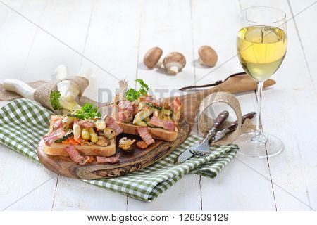 Toast with fried white asparagus, other vegetables and bacon on a wooden board, served with a glass of white wine