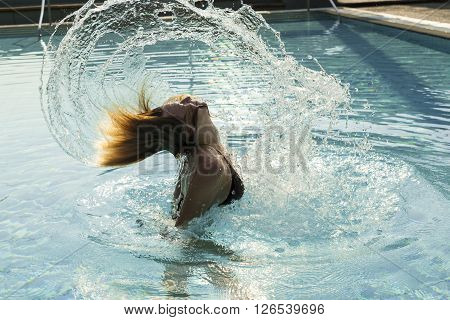 Beautiful blond girl having fun at the swimming pool swaying sway with her head making a water splash with her hair