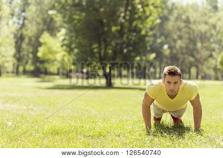 Young sportsman working-out in a park doing a series of pushups
