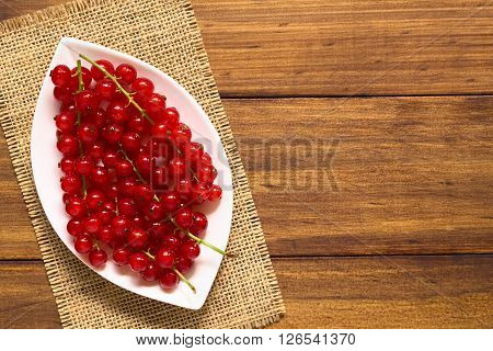 Raw red currants (lat. Ribes rubrum) on plate photographed overhead on dark wood with natural light