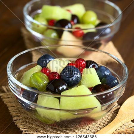 Fresh fruit salad made of cantaloupe melon blueberry redcurrant gooseberry and sweet cherry in glass bowls photographed on dark wood with natural light (Selective Focus Focus in the middle of the first salad)