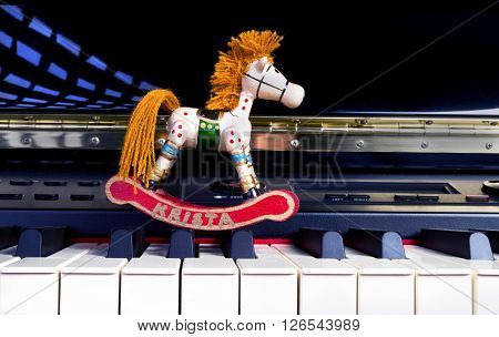 Toy wooden horse on a digital piano.