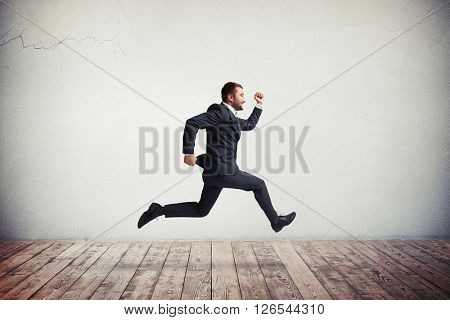 Young handsome Caucasian man in formal wear running and jumping with happy smile