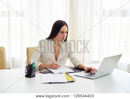 Young woman working on her laptop and writing some data in a pad in white office