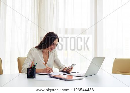 Smiling young beautiful woman working at her smartphone and holds a hand near the head in the modern spacious office