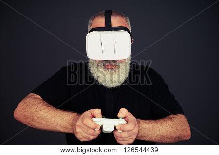 Beard senior man is playing on the joystick wearing hi-tech VR headset, on black background