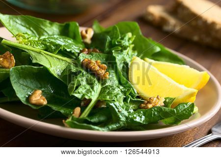 Fresh spinach and walnut salad with lemon wedges on the side served on plate photographed with natural light (Selective Focus Focus on the walnut in the middle of the image and the one in front of the lemon)