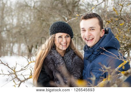 Happy Young Couple In Winter Garden