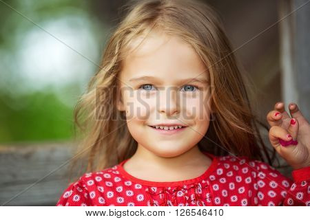 Countryside portrait of happy little girl in red dress