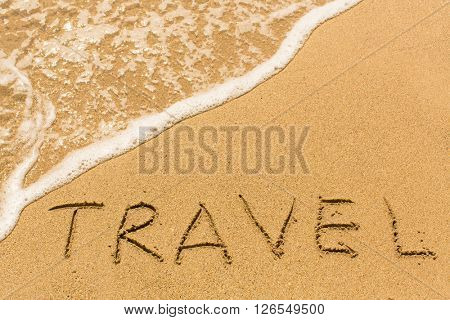 Travel - inscription by hand on yellow beach sand.