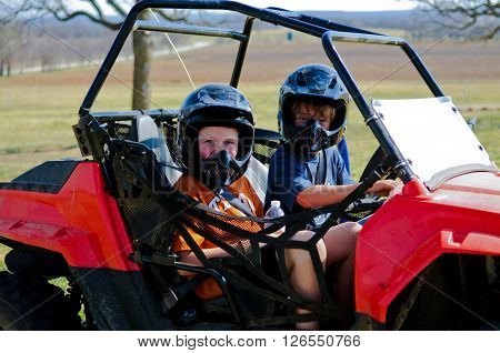 Happy boy and girl riding a dune buggy out in the country.