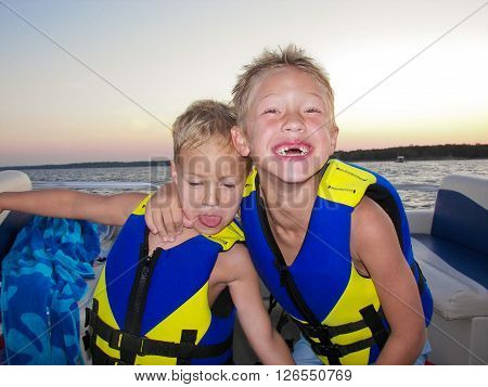 Young boys in life jackets smiling big on a lake boat at sunsest.
