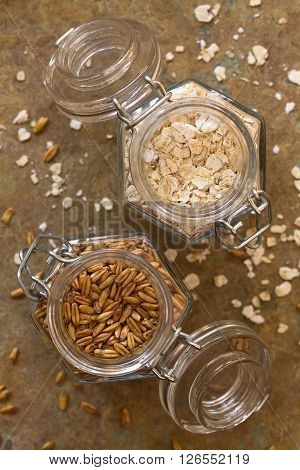 Toasted oat grains and oat flakes in swing top jars photographed overhead on slate with natural light (Selective Focus Focus on the top of the oats)