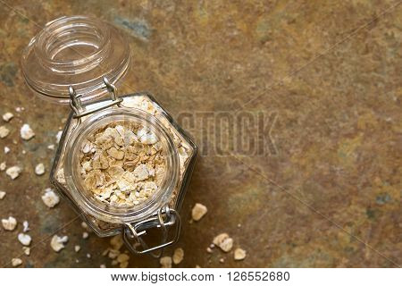 Oatmeal in swing top jar photographed overhead on slate with natural light (Selective Focus Focus on the top of the oatmeal)