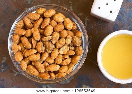 Peanuts with honey and salt in glass bowl salt and honey on the side. Photographed overhead on slate with natural light