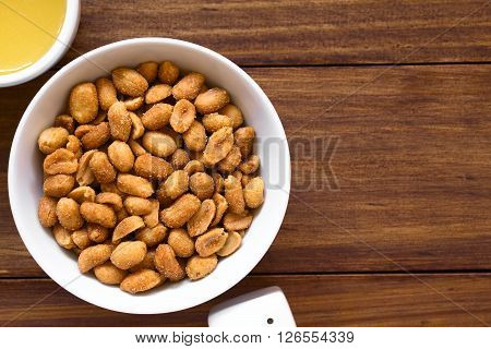 Peanuts with honey and salt in bowl salt and honey on the side. Photographed overhead on dark wood with natural light