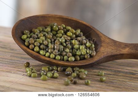 Soya bean pulses in a wooden spoon and scattered