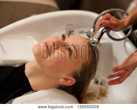 Hair Stylist At Work - Hairdresser Washing Hair To The Customer Before Doing Hairstyle In A Professi