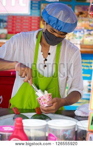 Phuket Thailand - April 17 2016: The typical seller of ice cream on the street of Phuket, making tasty ice cream