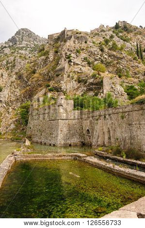 Kotor old town north defensive walls and Scurda river with St. John's fortress on top of the hill