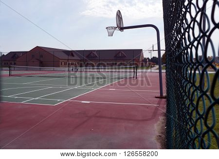 One may play either tennis or basketball in a public court in Plainfield, Illinois.