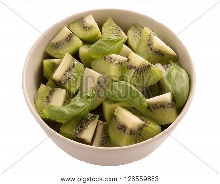 Kiwi fruit sliced segments in a round bowl isolated on white background