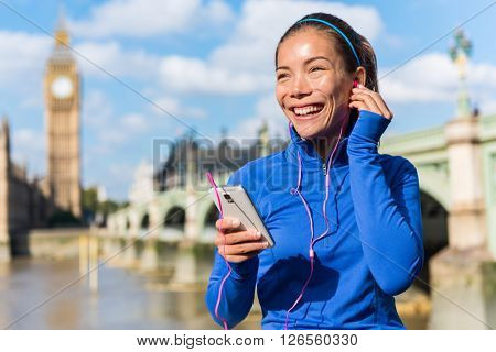London running lifestyle woman listening to fitness music playlist on smart phone. Female going for run training in urban city street. Runner girl near Big Ben, Westminster Bridge, London, England, UK