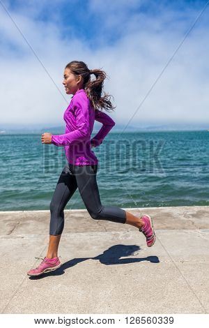 Woman running on waterfront harbour pier in San Francisco, California, USA. Mixed race fit fitness sport model in spring / autumn running clothing outfit. Smiling happy female athlete runner training.