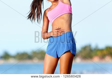 Side stitch stomach pain. Woman runner cramps. Jogging girl with stomach side pain during jogging work out. Female athlete on beach.