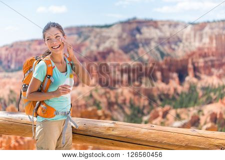 Hiker sunscreen. Woman hiking putting sunblock lotion outdoors during summer hike holidays. Mixed race Caucasian Asian female model. Bryce Canyon National Park, Utah, United States.