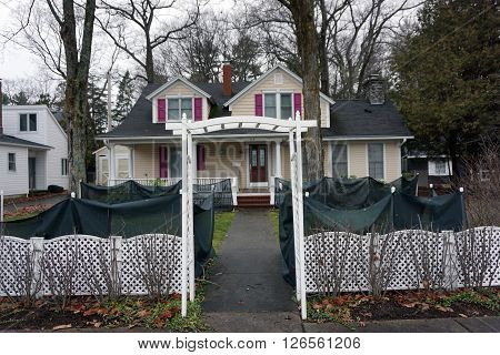 HARBOR SPRINGS, MICHIGAN / UNITED STATES - DECEMBER 23, 2015: An arbor gate stands in front of a home on Traverse Street in Harbor Springs.