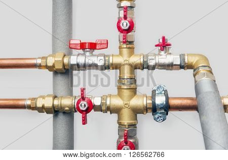 Heating system's cooper pipes with ball valves on a grey wall