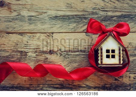 plywood small house with red ribbon on old wooden table