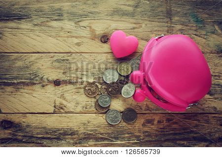 pink silicone purse with coins and heart of rubber on a wooden table
