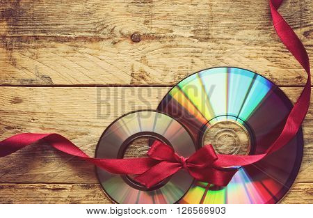 two CD disks and ribbon with bow on a wooden table