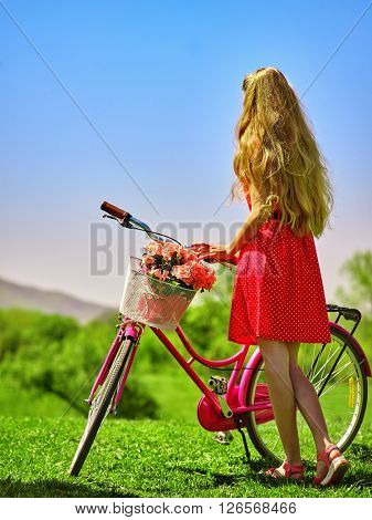 Girl wearing red polka dots dress rides bicycle into park.