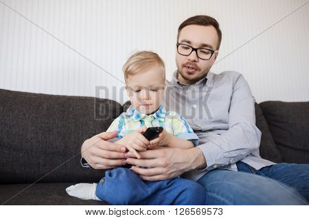 family, childhood, fatherhood, technology and people concept - happy father helping little son with remote control and watching tv at home