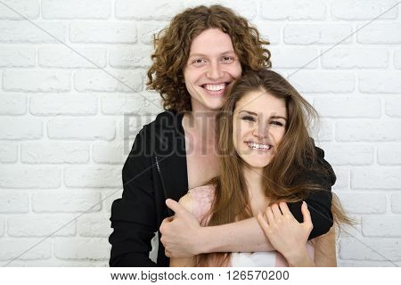 Portrait of young contented couple. Young man and woman embracing each other, studio shot. Psychology of relations, heterosexual couple, tenderness, feeling, caress concept.