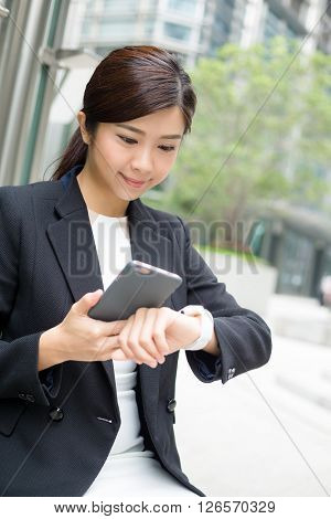 Businesswoman connecting cellphone and smart watch