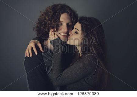Portrait of young contented couple. Young man and woman embracing each other and kissing, studio shot. Psychology of relations, heterosexual couple, tenderness, feeling, caress concept. Image toned.