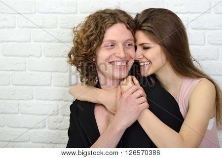 Portrait of young contented couple. Young man and woman embracing each other and kissing, studio shot. Psychology of relations, heterosexual couple, tenderness, feeling, caress concept.