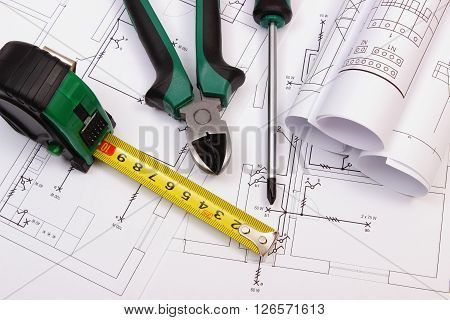 Metal pliers screwdriver tape measure and rolls of diagrams on electrical construction drawing of house work tool and drawing for engineer jobs concept of building house